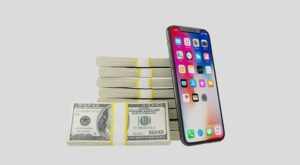 bundles of cash next to a cell phone