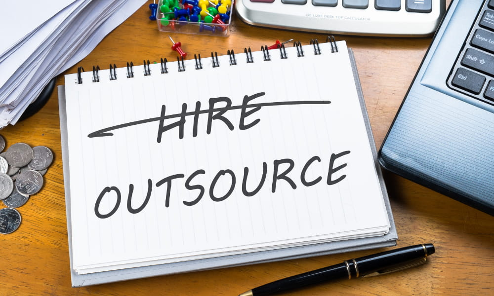 The word hire crossed out on paper and outsource written