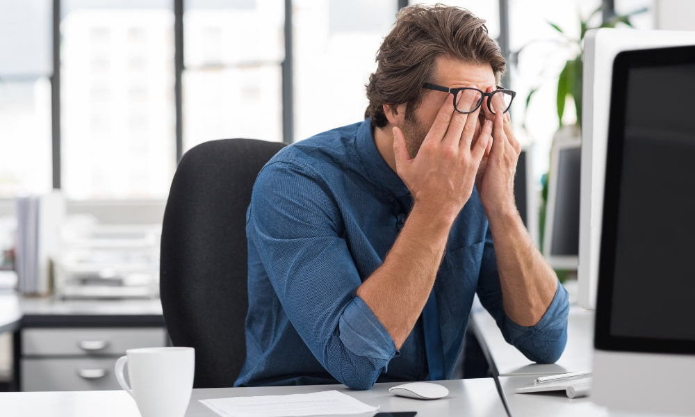 Tech employee frustrated from scope creep at his computer